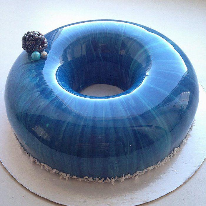 """Já ouviu falar dos bolos com cobertura de vidro? São a nova mania na internet, e tudo por """"culpa"""" de uma confeitura russa que além de fazer bolos maravilhosos também é um excelente fotógrafa. As imagens dos bolos são maravilhosas, mas os mestres da culinária revelam o truque: gelatina! Isto mesmo, um ingrediente que todo"""