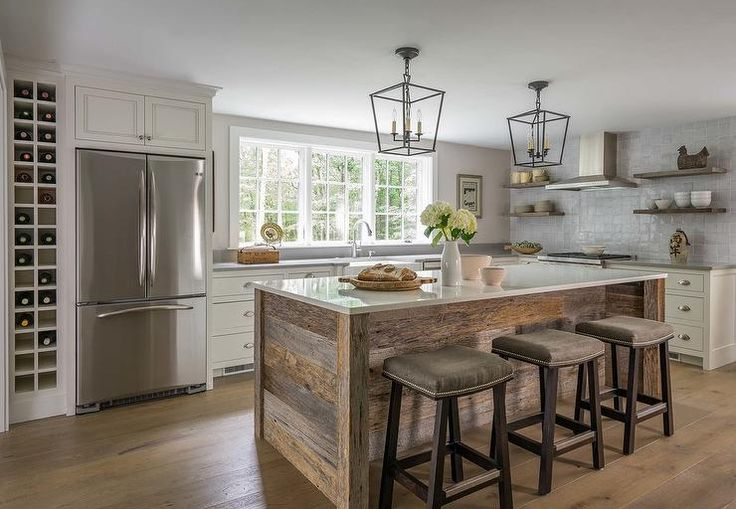 White and gray kitchen accented with rustic wood accents is lit by mini Darlana pendants hung over a rustic wood plank island seating three backless gray linen island stools at a light gray quartz countertop.