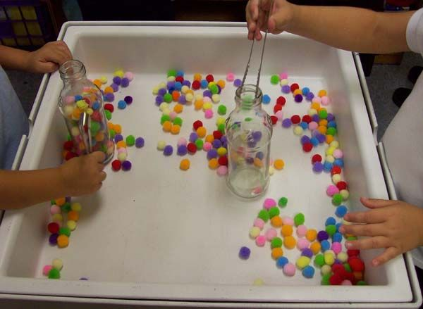 Children use the tongs to pick up the colored pom poms and drop them into a bottle. This activity is good fine motor practice and hand-eye coordination.