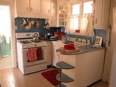 Super cute, retro 1950's kitchen. White cabinets, with red or green instead of blue? Pots & pans hung right there above the stove? Yes please, this is an image to hold on to.