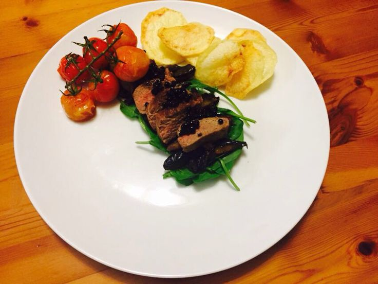 Hanger steak on a bed of baby spinach and black mushrooms topped with balsamic beads served with vine tomatoes and crispy potato