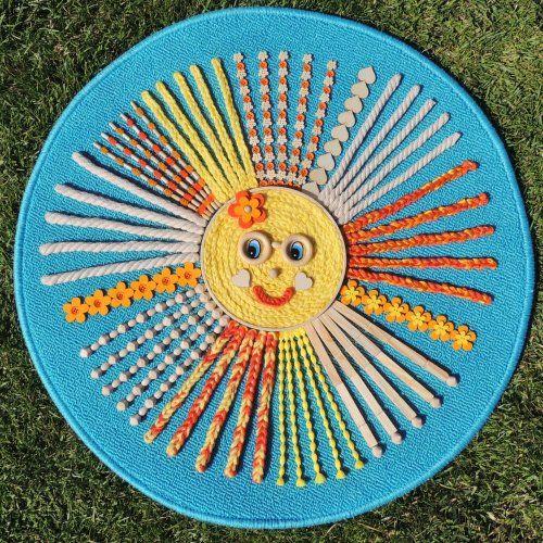 """Senzomotorický kobereček ke stimulaci chodidel dítěte. Podkladem je kvalitní kobereček se spodní protiskluzovou vrstvou, který je pokryt bavlněnou kroucenou šňůrou, vlnou, dřevěnými korálky a jinými dřevěnými prvky, plstěnými kytičkami a knoflíčky. """"Hlava"""" sluníčka je z bambusového kola."""