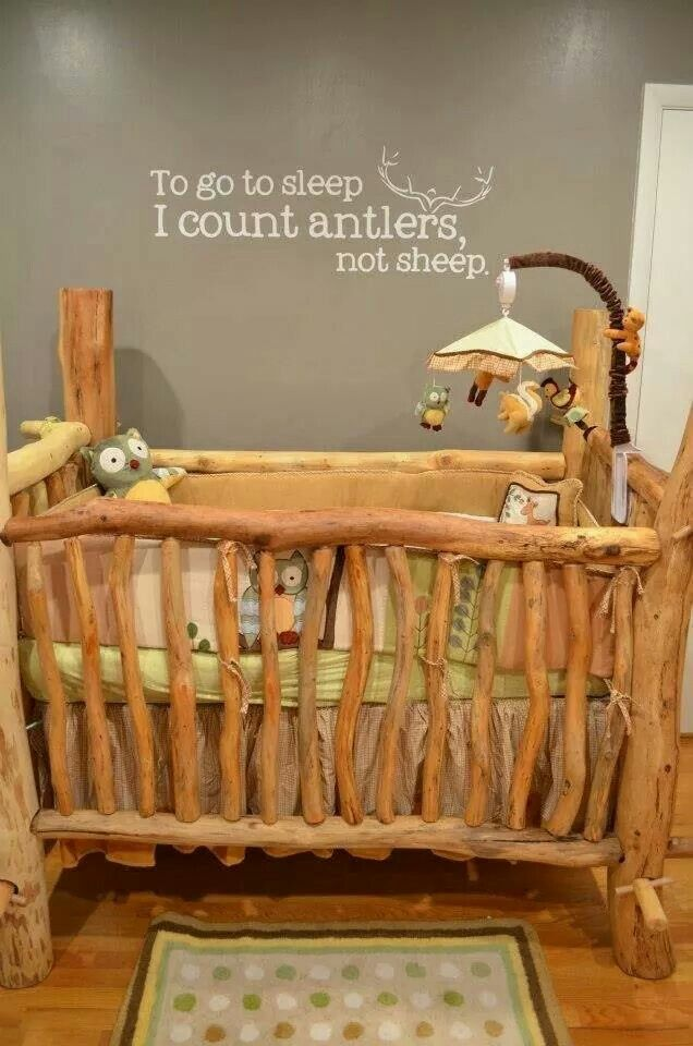 Wooden baby crib made of tree branches. Not crazy about the decal on the wall but loving the natural look of the crib!