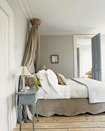 Cette chambre new-yorkaise est décorée entièrement dans le style gustavien.  Les couleurs employées sont neutres: le blanc (plafond, porte, literie), le gris clair (mur du fond), le beige chamois (jupon et tête de lit, rideaux et coussins) et la petite note froide de bleu (la table de nuit) en contrepoint. Crédit photographique: Martha Stewart