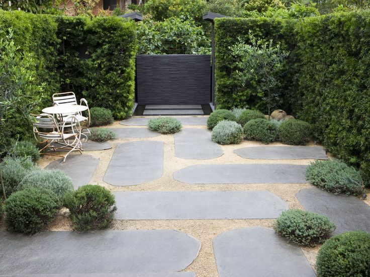 A dense, dark green screen forms a protective back drop to this courtyard of spheres, large blue stone stepping stones all looking sculptural by a base of decomposed granite.  Three Olive trees cast an evergreen filtered show from above while Frangipanis in pots connect this garden to its coastline location.  The hedge on the perimeter stops either side of a wet feature wall and pond, drawing the perspective and encouraging the eye to glimpse to the view on the world outside.