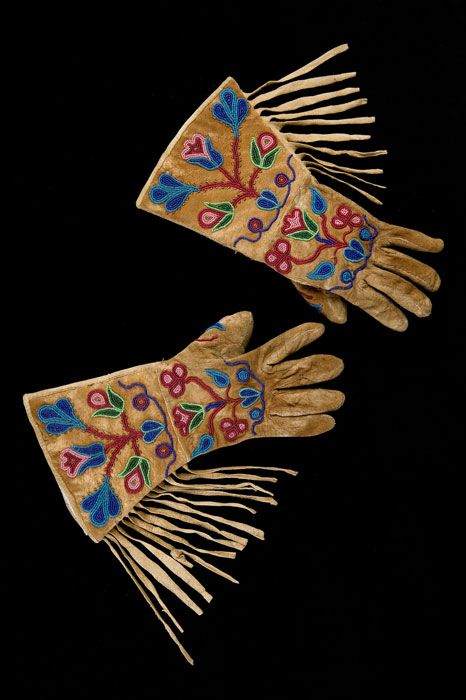 Gauntlets. Nakoda. ca. 1890.On this pair of gauntlets, stylized floral motifs in rich colours stand out against the golden brown of the smoked hide.