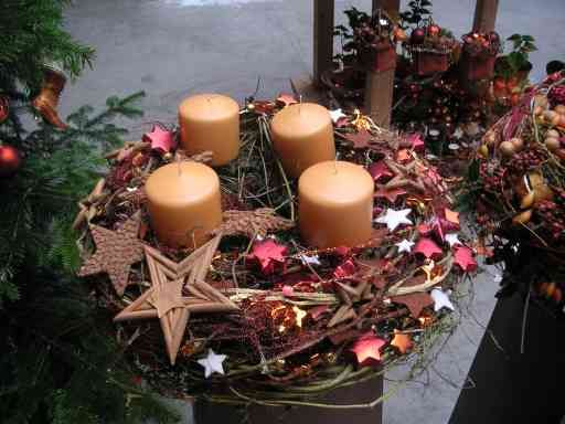 Adventni venček in zvezdice v različnih velikosti. Umirjena barva svečk pozornost preusmerja prav na zvezde.