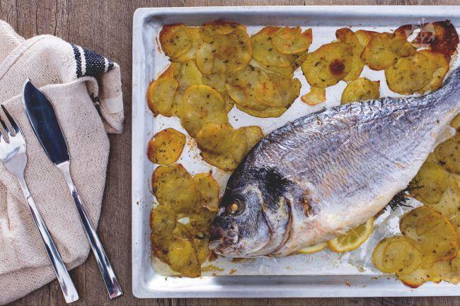 L'orata al forno è un secondo piatto di pesce classico e saporito, preparato con un contorno di gustose patate a fette.
