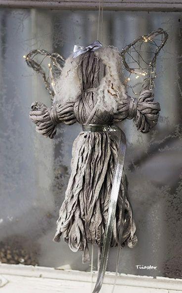 Valoenkula hopeaisella nauhalla. Suloinen, kokonaan kankaasta valmistettu villikiharainen enkeli loistaa kauniisti ikkunassa tai seinällä. Siivet taivuteltu käsin metallilangasta, patterivaloissa lämmin sävy. Ihastuttava lisä etenkin jouluiseen sisustukseen!  Adorable curly-haired angel, completely made from fabric except her beautiful wings which are hand bent from metal wire. Battery lights shine in a warm shade. Nice add to your christmas decorations, for example!