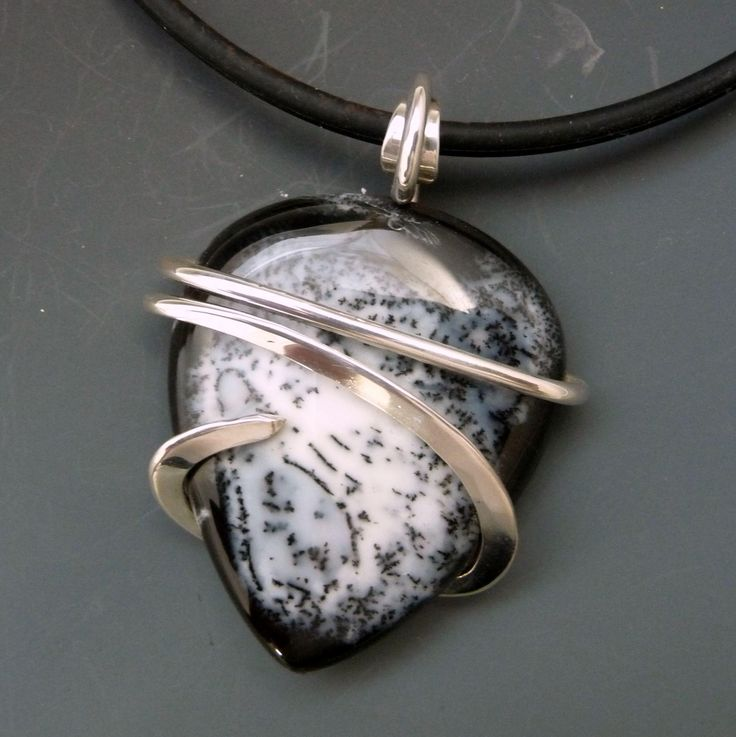"""Dendrite Agate Sterling Silver Wrapped Pendant Necklace  Dendritic Agate is a chalcedony containing branch or fern-like markings called dendrites. A striking Dendrite Agate teardrop pendant that I wrapped as simply as possible using cold forming techniques to keep the highlight on the beautiful black and white stone. The pendant measures approximately 45x35mm (2 1/4"""" from top of bail) and comes complete with an 18'' Black Silicone Rubber 3mm Tubing Cord Necklace with Locking Clasp.  Every…"""