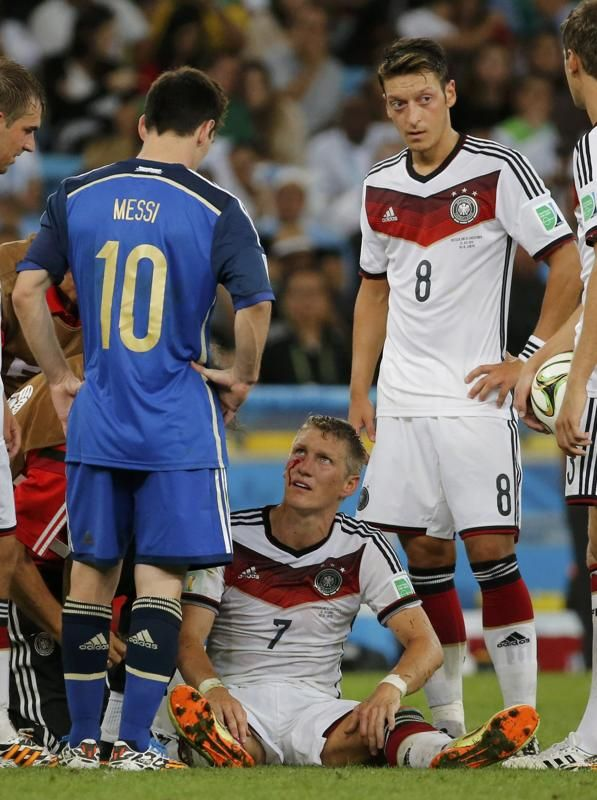Germany's Bastian Schweinsteiger sits in the pitch injured after colliding with Argentina's Sergio Aguero during extra time in their 2014 World Cup final at the Maracana stadium in Rio de Janeiro July 13, 2014. REUTERS/Sergio Moraes