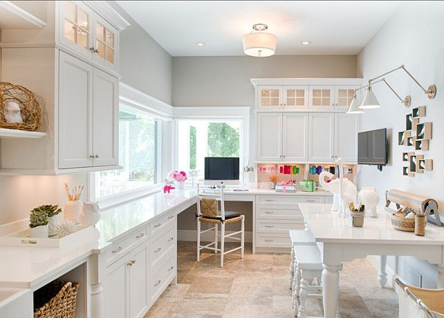 "Craft Room. Designed by Studio M Interiors. This well-designed and fully-equipped craft room is perfect for family living. Gorgeous built-in white cabinets and glass upper cabinets paired with nickel hardware and white quartz counters alongside gray walls illuminated by a semi flush mount drum pendant, ""Quoizel Deluxe Semi Flush Mount"".   Paint Color: ""Benjamin Moore Apparition"". . #CraftRoom #CraftRoomDesign #CraftRoomIdeas"