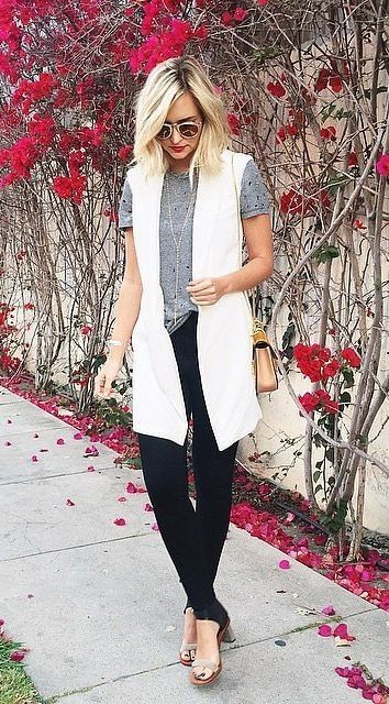 A long white vest, a grey t-shirt, and black skinny jeans