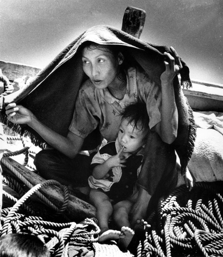 A Vietnamese woman uses a blanket to shelter herself and her child from the hot sun aboard a refugee boat in Nov. 1977. They are among 50 refugees aboard a 30-foot fishing boat in the Gulf of Siam looking for freedom in Thailand. (AP Photo/Eddie Adams)