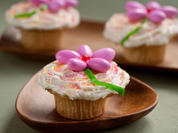 Easter Flower Cupcakes : Echo the bright hues of spring's first blossoms with arrangement of pink candy-coated Jordan almonds. Fruit leather forms the stem, and sanding sugar adds sparkle to the fluffy icing canvas. via Food Network