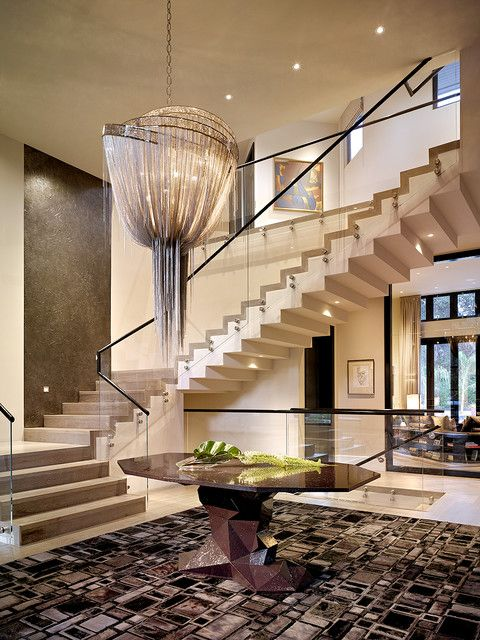 : Imposing Semi Swirly Staircase With Glass Balustrade Set As Background Of Home Hall With Chandelier Above Table