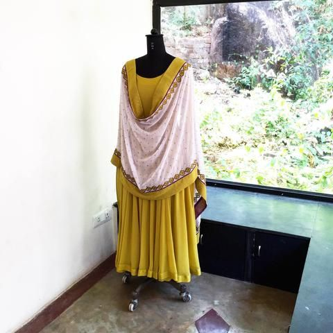 This anarkali is pure grace. The neckline and hem are beautifully textured with stitch lines. The piece is made of Modal and lined with malmal. The gher falls flat. This make it extremely figure friendly. The dupatta is in georgette and has been hand embroidered with bullen technique. It comes with leggings.