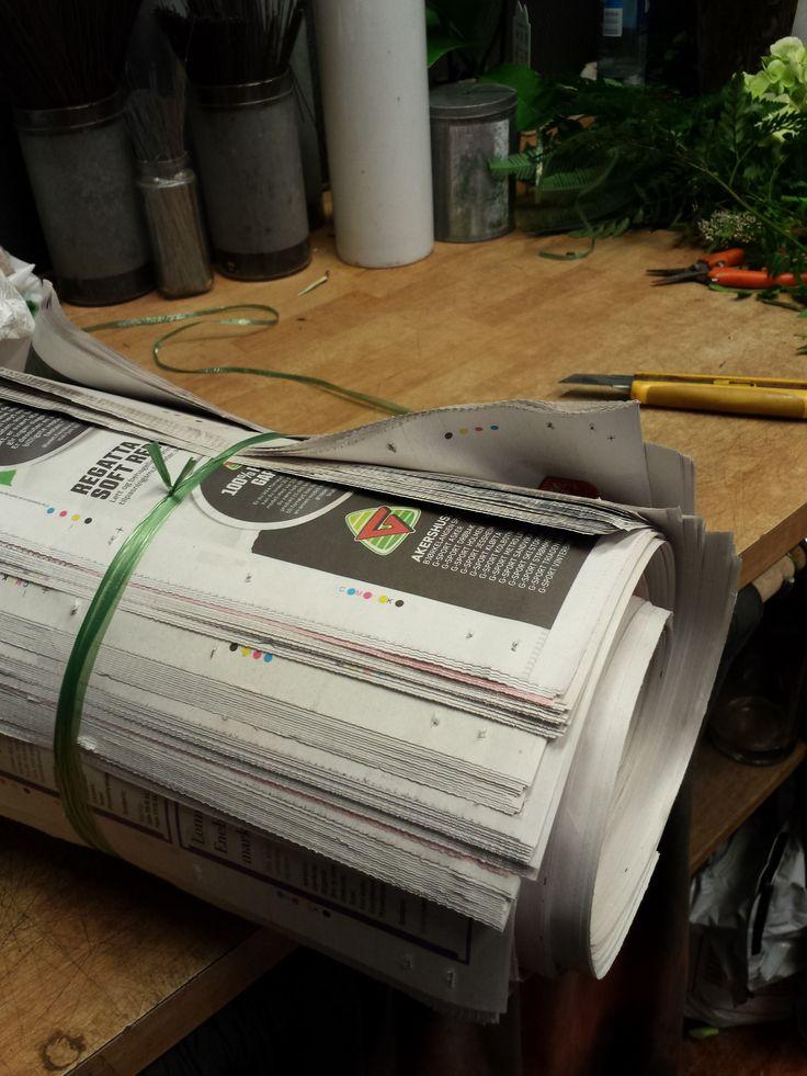Ruller alle ferdige aviser sammen siden det er ikke mere plass i hyllen under disken.