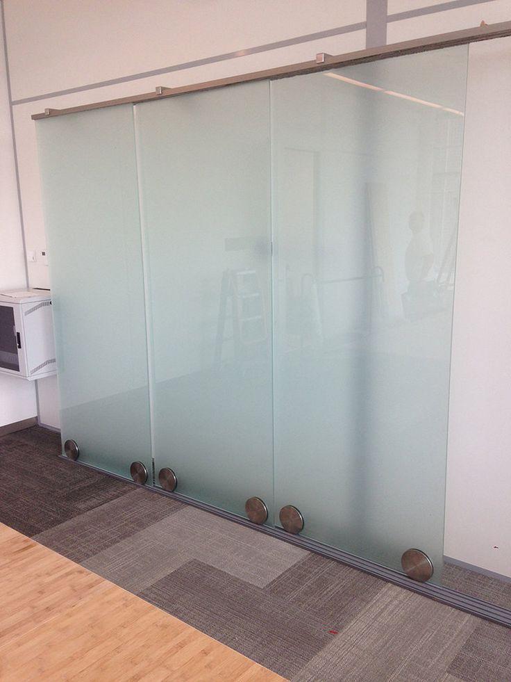 Glazen schuifdeuren in satijnglas die dienen als scheidingswand. In dit geval worden ze ook gebruikt als whiteboard in een vergaderruimte.