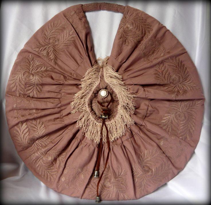 Napkorong körtáska -Handmade by Judy Majoros: Igazán egyedi ez a hímzett körtáska. Alapja hímzett szövet, belseje kordbársony. A táska két félkör műanyag merevítővel készült, így középen összehajtható. Eleje rojttal, díszgombbal, és zsinórral díszített, hátulja selyembéléssel fedett, és steppelve van a belső kordbársony anyaghoz. Hátsó részén található cipzárral záródik, pakoló része zseb szerűen van megoldva, emellett egy hímzett, gombbal záródó zseb is található rajta.