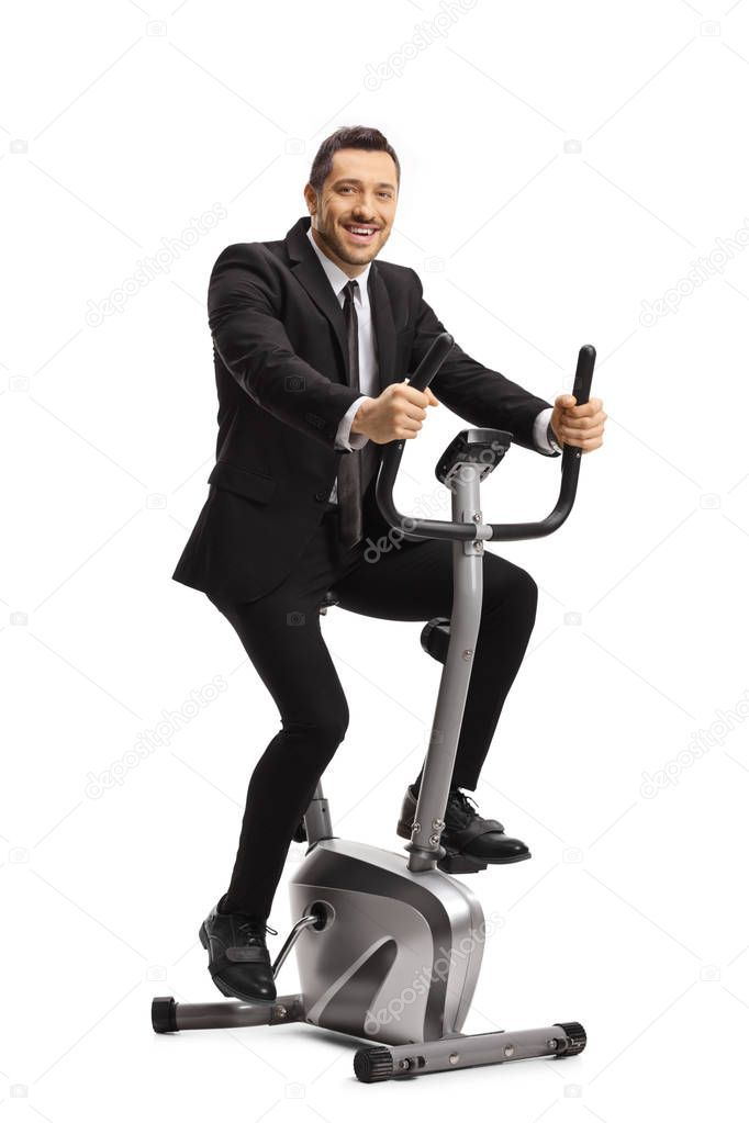 Cheerful Young Businessman Exercising On A Stationary Bike Stock