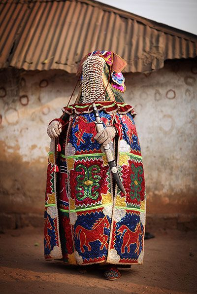 Africa   The Egungun wear flamboyant sequin-spangled capes adorned with animal and human motifs. Their faces were veiled by cowry shell screens and it is said to be bad luck if you see their eyes.  Eyewitness:  Voodoo style, Ouidah, Benin.   © Dan Kitwood