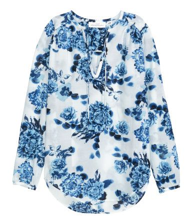 White floral. Long-sleeved blouse in an airy viscose and cotton weave with a V-neck with a tie, pleats at the shoulders, a pleat at the back and a rounded