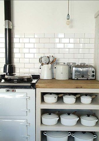 wood burning white oven and cast iron cookware under wood countertop