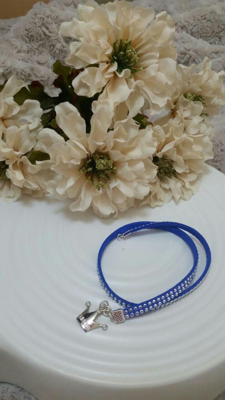 Pulsera gamuza azul con dije corona plateada.