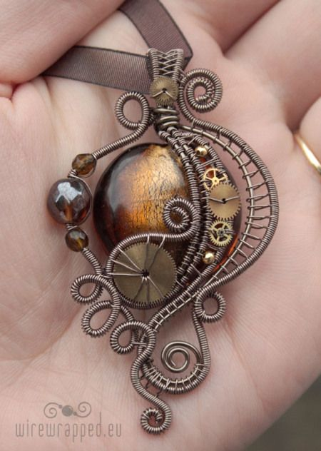 Victorian styled Steampunk pendant with polished glass, wire wrapping and watch parts.