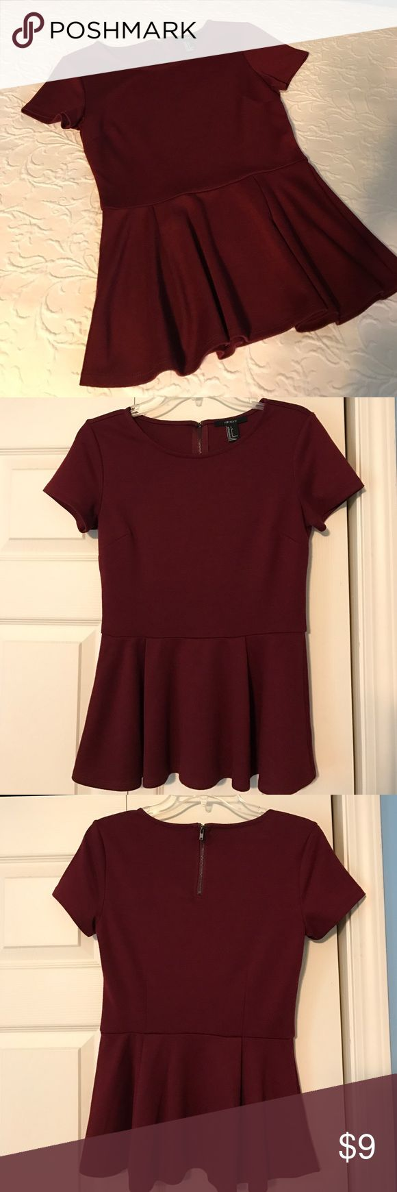 Burgundy Peplum Short-sleeve Top This burgundy peplum would look beautiful with jeans or a skirt. It's a quality made top and the peplum hits where it's most flattering. Has a zipper and clasp, which is rare to find on a top. Comfortable material and flattering silhouette. Forever 21 Tops