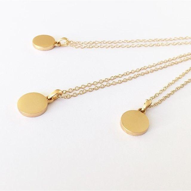 Plate necklace fra f.eks. Bjørklund eller Secrets by B, eller tilsvarende. Gullfarget smykke med rund plate til gravering; bokstaven V
