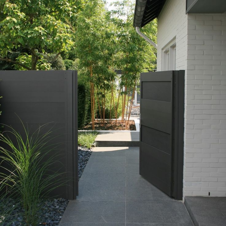 Poort en schutting met toegang tot moderne tuin van basalt en aluminium