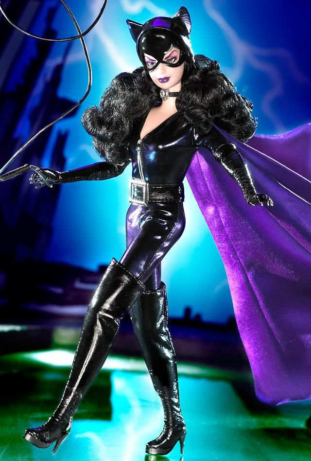 Barbie as Catwoman is purrrr-fect in her purple catsuit topped with a striking cape! A black belt with silvery buckle and black boots are boldly utilitarian. Her sculpted hands feature cat claws. She wears black gloves and a black ribbon choker with silvery charm. Finally, a purple and black mask with cat ears mark her as the ultimate Feline Fatale. NEEEEEED