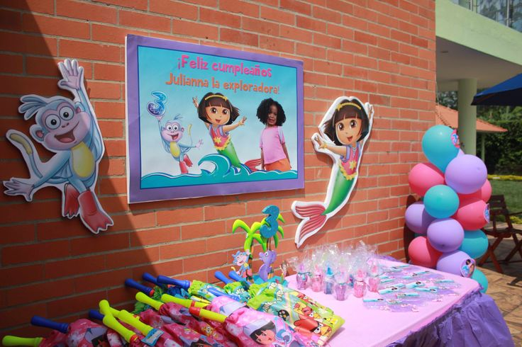 My little #girl 's #Dora #Mermaid #Adventure #pool #birthday #party - I mounted the #personalized #party #sign and #dora #boots #cutouts and mounted them on #styrofoam, which I taped to walll using thick double-sided tape. #doratheexplorer #doralaexploradora #dora #explorer #exploradora #mermaid #sirena #adventure #reino #mermaidadventure #pool #piscina #party #fiesta #partyideas #ideas #crafting #kids #kidsbirthdayparty #birthday #birthdayparty #decorate #decoration