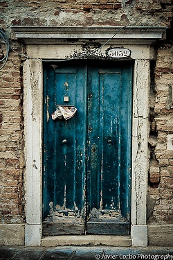 I think turquoise/blue-green is a popular color for doors. I agree. Love the distressed rustic look of this.