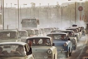 In a giant cloud of exhaust fumes of two-stroke engines, hundreds of East German cars wait bumper to bumper in front of the West German chec...