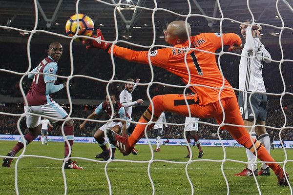 Juan Mata (C) scores the opening goal past West Ham United's Irish goalkeeper Darren Randolph during the English Premier League football match between West Ham United and Manchester United at The London Stadium, in east London on January 2, 2017..Manchester United won the game 2-0. / AFP / Adrian DENNIS / RESTRICTED TO EDITORIAL USE. No use with unauthorized audio, video, data, fixture lists, club/league logos or 'live' services. Online in-match use lim...