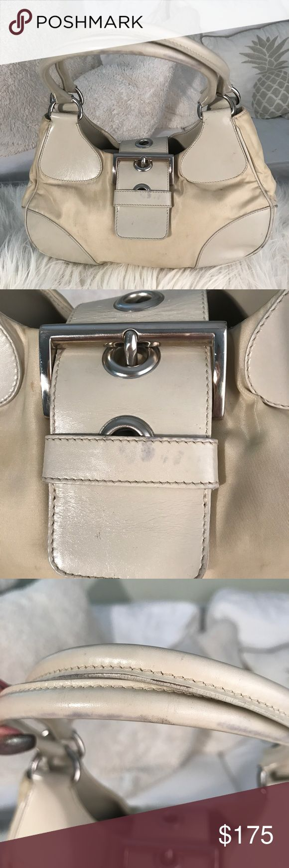 GUC Prada Buckle Bag AUTHENTIC GUC Prada Buckle Bag AUTHENTIC Cream with silver hardware. Purchased from Neiman Marcus. See photos for typical wear and tear. Interior is practically perfect no rips tears stains or other flaws. Exterior has some wear on handles and other areas of leather and one small spot on the side of the fabric which has never been treated or removal attempted. Feel free to ask questions. Price reflects condition not authenticity. Original purchase price $1298. Dust bag…
