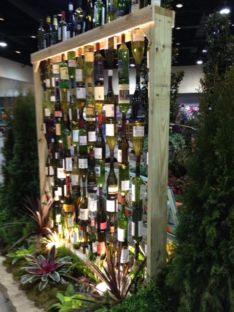 It looks like you would just have to drill a hole in the bottom of the wine bottle and then run a rope through the top and bottom of the bottles to make the wall.  It looks great!