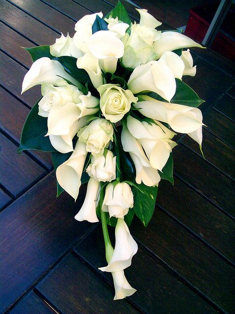A cascading lily bouquet with the stems wrapped in lace, tied with a twine bow, then finished with a pearl straight pin. Finish the bottoms with pearl straight pins, as well.