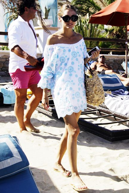 Socialite Olivia Palermo might be having the most fashionable summer vacation in history. While on holiday with friends in Mykonos, Greece on August 6th, Palermo spent some time soaking up the sun in a white and blue eyelit tunic with simple sandals, shades, and a straw beachbag.