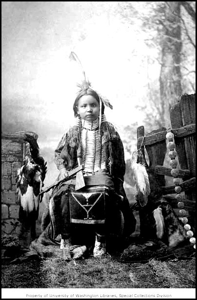 Ponca child in traditional regalia holding a tomahawk, Arkansas City, Kansas, ca. 1892.