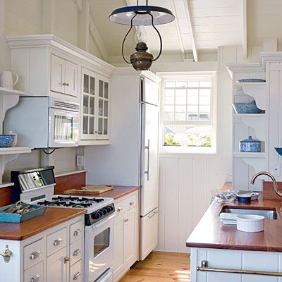 Sea-Inspired Space. A GALLEY-STYLE KITCHEN has easy-to-reach dishes on open shelves and stacked appliances for a space-savvy solution.