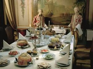 En vit damastduk, kandelabrar, en bordsplatta av fajans mitt på bordet med en skål fylld av frukt ... Det här festbordet är dukat enligt anvisningar från Johan Winbergs Kok-Bok som kom ut 1761. Här finns spansk tårta, kalvstek, kalkon, glaserad skinka, en aladåb, kronärtskockor, gröna bönor och champinjoner med kräftstjärtar. Här finns också Schiemerta, ägg som egentligen är fiskbullar. Det var högsta mode att laga rätter som såg ut att vara något annat än de egentligen. Foto: Mats Landin…