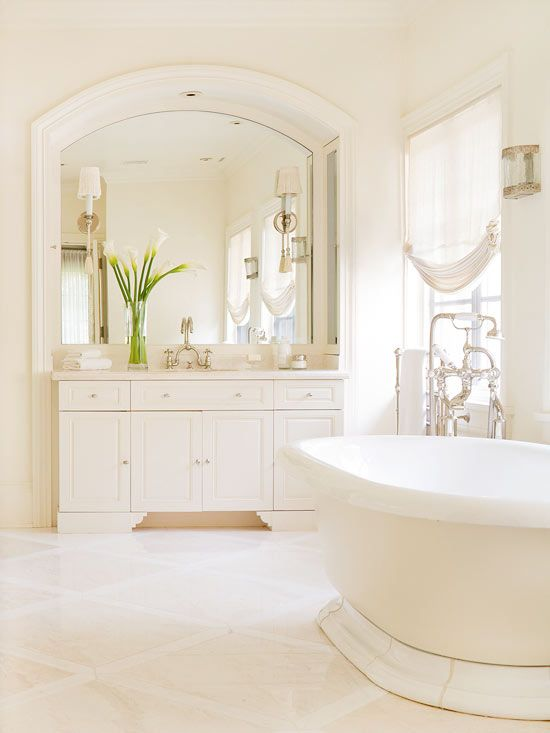 """""""Ivory and white tile floors coordinate with creamy walls to create a space lovely in its simplicity. A large arched mirror crowned with white trim both expands and adds architectural value to this bathroom, while a stately freestanding tub and vintage faucet complete the elegant look."""" The mirror is the highlight to this design for me."""