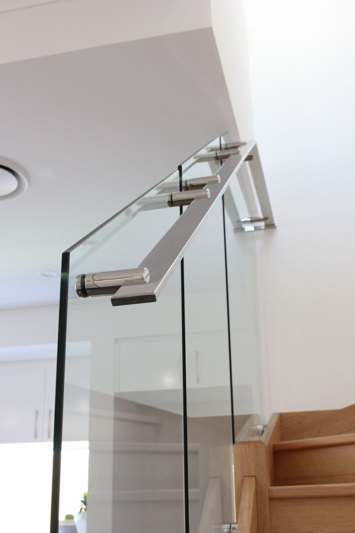 Glass staircase featuring stainless steel handrails and standoffs
