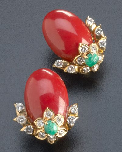 Red coral and diamond earrings with emeralds in 18k yg. Oval coral cabochons supported by floriform diamond and emerald clusters. Diamonds: approx. 2.2 cts. TW.; coral: 24.5mm x 16.5mm each.