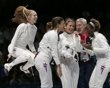 Susie Scanlan (L), Kelley Hurley (2nd L), Courtney Hurley (C) and Maya Lawrence of the U.S. (R) celebrate their victory with their coach at the end of the women's eppe team bronze medal fencing competition against Russia at the ExCel venue during the London 2012 Olympic Games August 4, 2012.