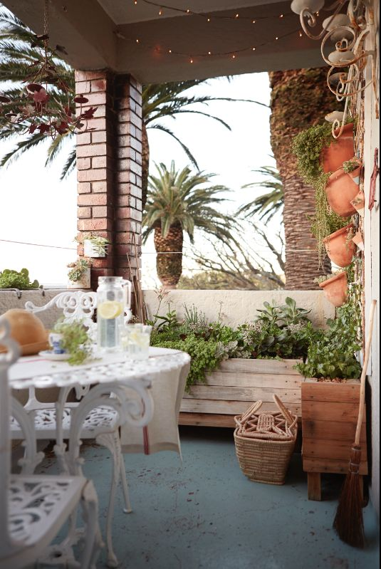 By Simone Borcherding stylist   writer   spacemaker. Small spaces patio verandah with fairy lights, cast iron table and chairs, hanging terracotta pots and wooden crate planter boxes.